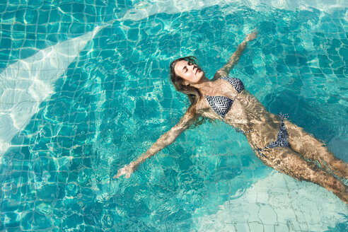 Woman floating on water of a swimming pool - SBOF000006