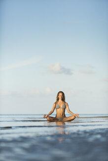 Thailand, woman meditating on beach - SBOF000015