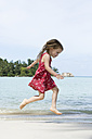 Thailand, girl in red dress jumping on beach - SBOF000018