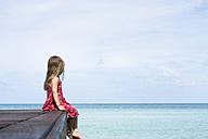 Thailand, girl in red dress sitting on jetty at the sea - SBOF000021