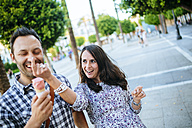 Couple having fun while eating an ice cream cone - KIJF000412