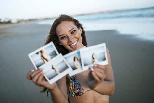 Young woman showing instant photos on the beach - KIJF000431