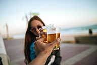 Clinking beer glasses by the sea - KIJF000434