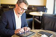 Businessman sitting in a coffee shop using digital tablet - MAEF011816