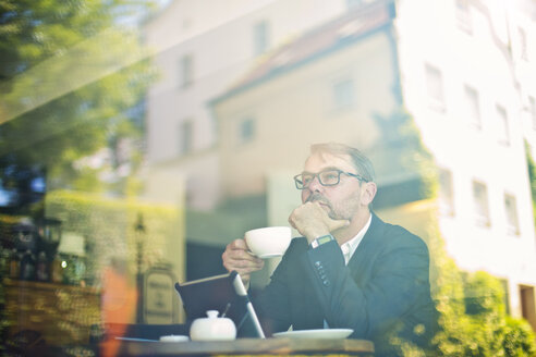 Pensive businessman with cup of coffee in a cafe behind windowpane - MAEF011819