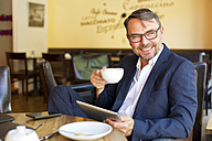 Portrait of smiling businessman with digital tablet sitting in a cafe drinking coffee - MAEF011822
