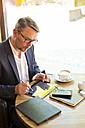 Businessman sitting in a coffee shop using digital tablet - MAEF011825