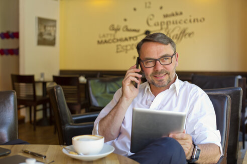 Portrait of smiling businessman with digital tablet sitting in a cafe telephoning with smartphone - MAEF011828