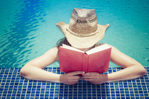 Woman wearing straw hat reading book at pool edge - CMF000479