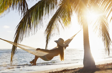 Dominican Rebublic, Young woman in hammock looking out over tropical beach - HSIF000461