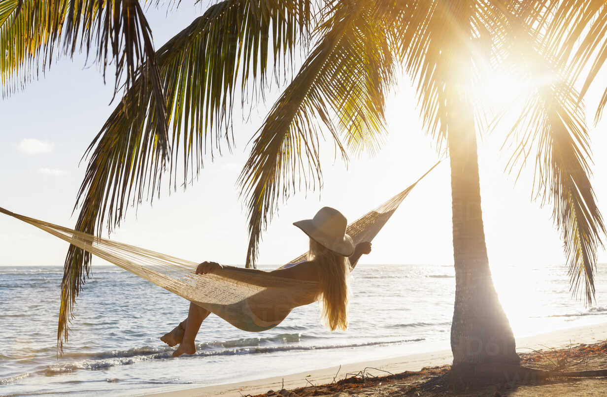 Dominican Rebublic, Young woman in hammock looking out over tropical beach - HSIF000461 - hsimages/Westend61