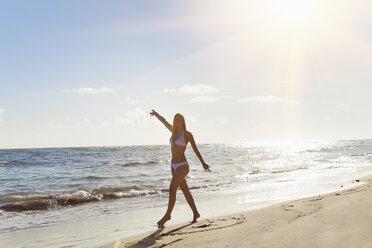 Dominican Rebublic, Young woman dancing along tropical beach - HSIF000464