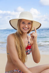 Young woman using sunscreen at beach - HSIF000482