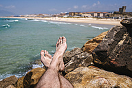 Spain, Andalusia, Tarifa, Close-up of feet on stones - KIJF000442