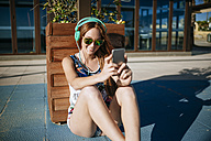 Young woman with headphones and mirrored sunglasses taking selfie with smartphone - KIJF000460