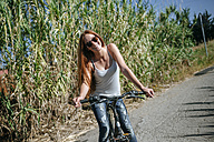 Happy young woman riding bicycle on country lane - KIJF000481