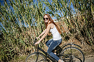 Happy young woman riding bicycle in the countryside - KIJF000484