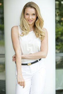 Portrait of smiling blond woman dressed in white - GDF001009