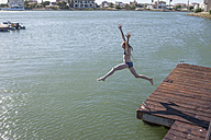 South Africa, Cape Town, girl jumping in water from jetty - ZEF008716