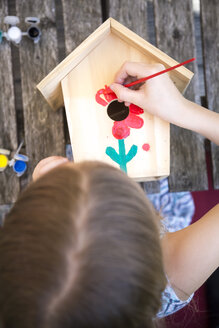 Girl painting red flower on a wooden birdhouse - SARF002770