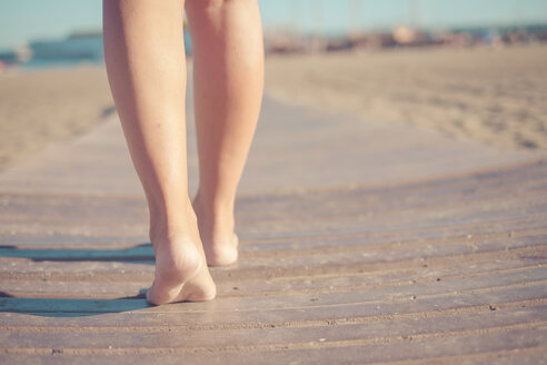 Legs of woman walking on boardwalk at the beach - SIPF000555