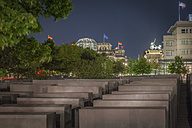 Germany, Berlin, Holocaust memorial with Reichstag and Brandenburger Tor in the background by night - NK000464