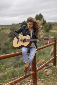 Woman sitting on wooden fence playing guitar - JPF000157