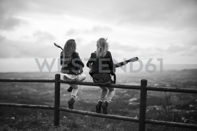 Two women sitting on wooden fence with guitars - JPF000160