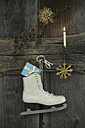 Christmas decoration and ice kate with present hanging on wooden wall - ASF005901