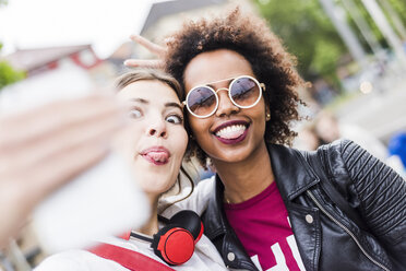 Two women sticking out tongues while taking selfie with smartphone - UUF007656