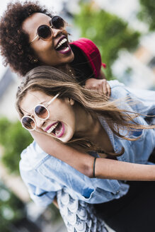 Laughing woman giving her friend a piggyback ride - UUF007677