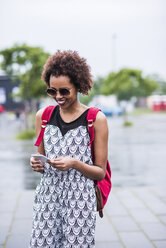 Portrait of smiling young woman looking at her smartphone - UUF007680