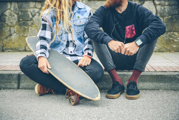 Couple with skateboard sitting on curb - DAPF000122