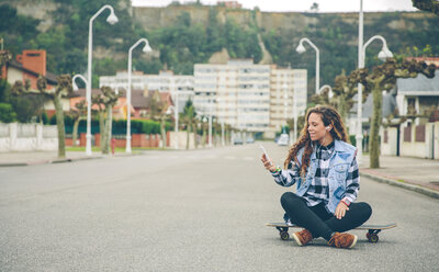 Young woman listening to music sitting on skateboard - DAPF000131