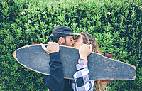 Couple kissing behind skateboard - DAPF000134