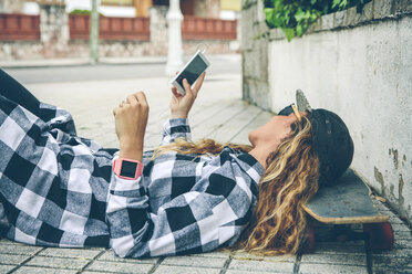 Young woman lying on skateboard looking at cell phone - DAPF000143