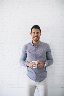 Young businessman standing against wall, holding cup up coffee - EBSF001451