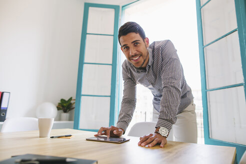 Young businessman using digital tablet in office - EBSF001463