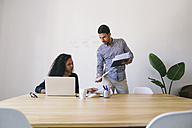Young businessman and woman working together in office, using laptop - EBSF001478