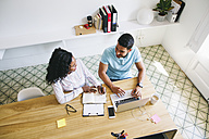 Young businessman and woman working together in office, using laptop - EBSF001508