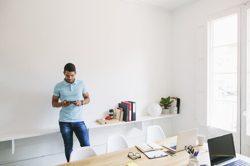Young businessman in office using digital tablet - EBSF001514