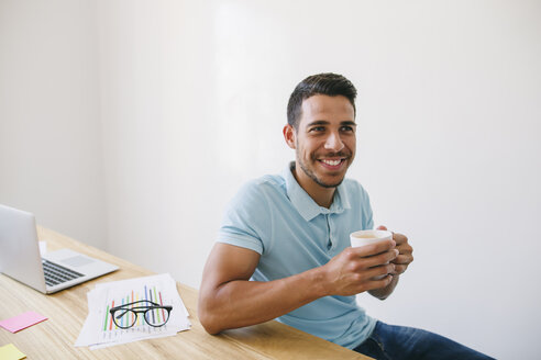 Young man in office drinking coffee - EBSF001538