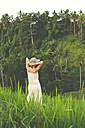 Indonesia, Bali, back view of woman wearing summer dress and hat in nature - KNTF000338