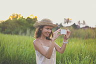 Woman taking picture with smartphone in nature - KNTF000350