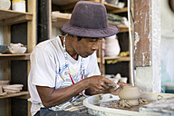 Man in workshop working on pottery - KNTF000363
