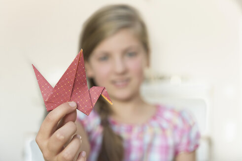 Girl showing origami bird - NHF001490