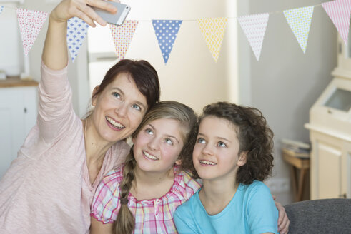 Happy mother and daughters taking a selfie - NHF001493