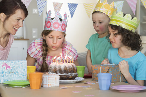Girl blowing out candles on birthday cake - NHF001502