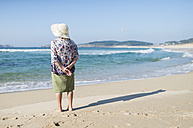 Back view of senior woman standing on the beach - RAEF001223