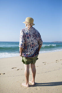 Back view of senior woman standing on the beach - RAEF001226